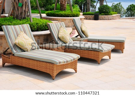 Picture of three chaise longues beside swimming pool. - stock photo