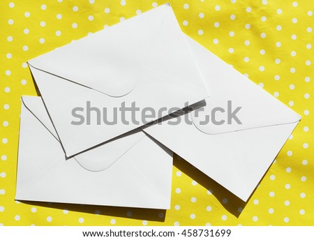 Picture of three white envelopes over yellow background