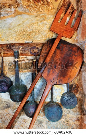 Picture of traditional oven and cooking utensils arranged against a stone wall