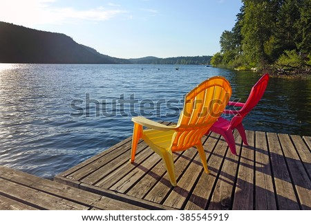 Picture of two adirondack chairs on a floating dock at St Mary Lake on Salt Spring Island,BC,Canada.