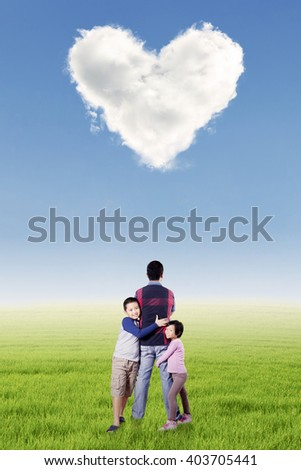 Picture of two cute children embrace their father on the meadow under cloud shaped heart symbol