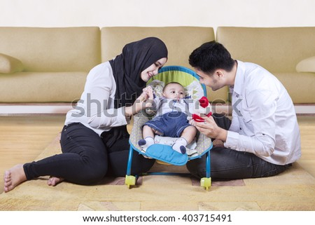 Picture of two happy parents playing with their baby in the stroller at home - stock photo