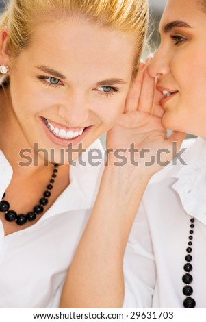 picture of two happy young girlfriends sharing secrets (focus on blonde) - stock photo