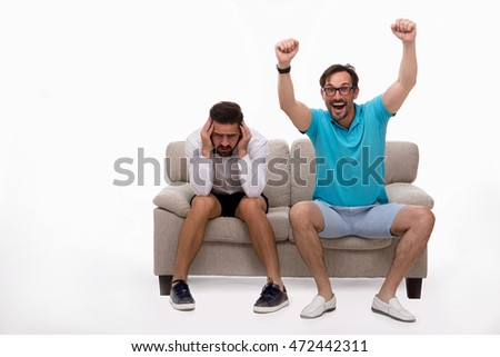 Picture of two men sitting on couch or sofa and looking at camera isolated on white background. Man in white shirt looking sad or disappointed. Emotions concept.