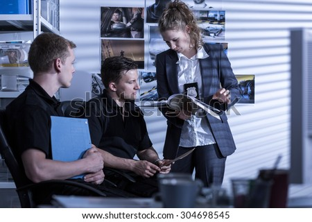 Picture of two policemen and policewoman on police station - stock photo