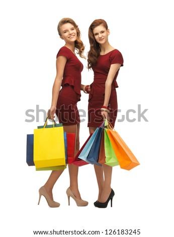picture of two teenage girls in red dresses with shopping bags - stock photo