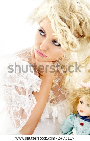 picture of unhappy bride holding doll over white - stock photo