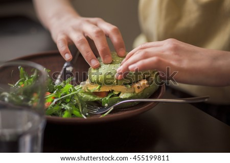 Picture of vegan dish represented on wooden plate. Lady's hands taking vegan burger from plate in vegan restaurant or cafe.