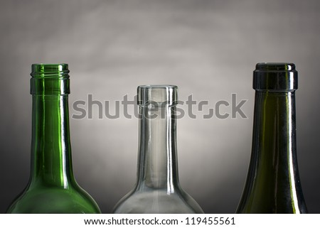 Picture of wine bottle necks on a row, on a grey and black background - stock photo