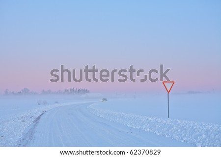 Picture of winter road with road sign and car in cold climate on sunset - stock photo