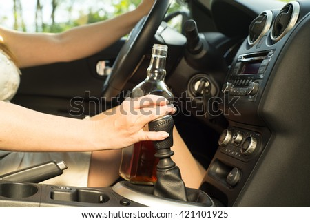 picture of woman drinking alcohol in the car.