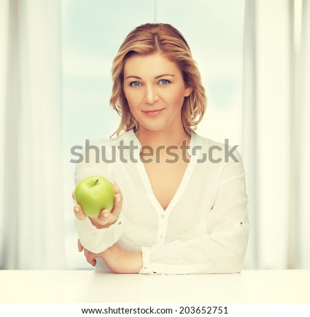 picture of woman in casual clothes with green apple - stock photo