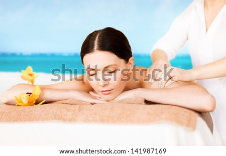 picture of woman in spa salon getting massage on the beach - stock photo