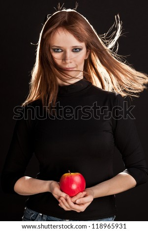 Picture of woman with smoky-eyes make-up holding a red apple - stock photo