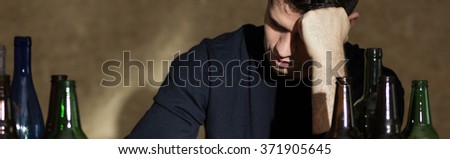 Picture of young alcoholic man and bottles - stock photo