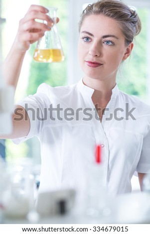Picture of young biotechnologist analyzing liquid substance in glass utensil - stock photo