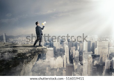 Picture of young businessman shouting by using a megaphone while standing on the cliff