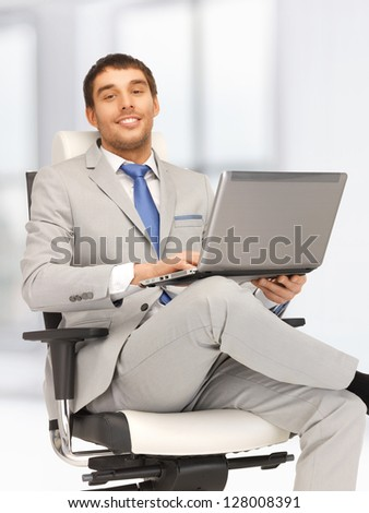 picture of young businessman sitting in chair with laptop - stock photo