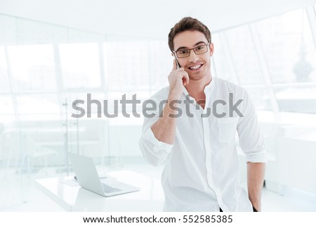 Picture of young cheerful man dressed in white shirt talking by mobile phone. Looking at camera.