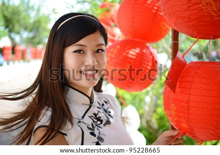 Picture of young chinese woman wearing traditional cheongsam with smiling face holding a red lantern