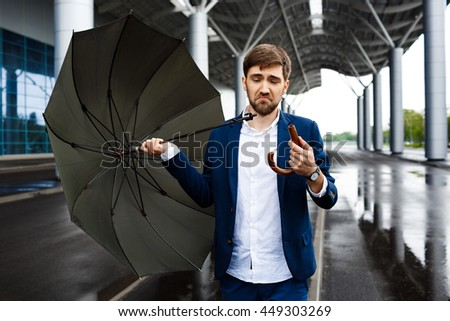 Picture of young confused businessman on street background holding broken umbrella
