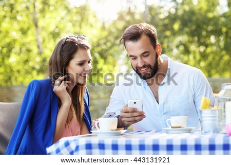 Picture of young couple using cellphone in a restaurant
