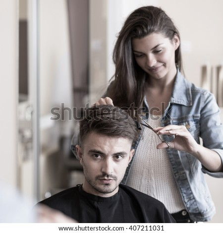 Picture of young female hairdresser and male customer - stock photo