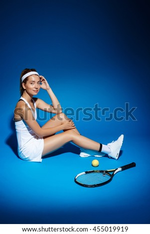Picture of young fintess girl near tennis racket and sitting on floor in studio - stock photo