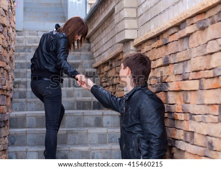 Picture of young man and woman outdoors (focus on woman) - stock photo