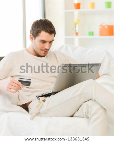 picture of young man with laptop and credit card at home