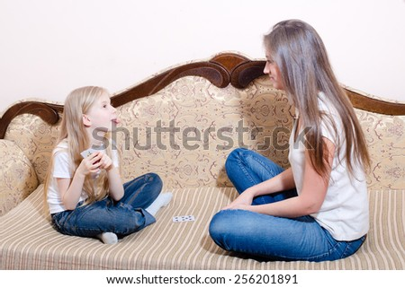 Picture of young pretty woman and little girl playing cards - stock photo