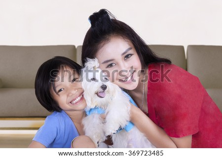 Picture of young woman and her daughter smiling at the camera while hugging a maltese dog at home - stock photo