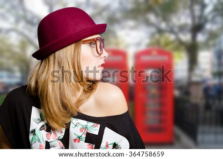 Picture of young woman in hipster glasses and pot hat with naked shoulder. Beautiful girl on London urban blurred background. - stock photo