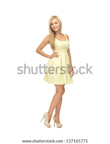 picture of young woman in yellow dress on high heels - stock photo