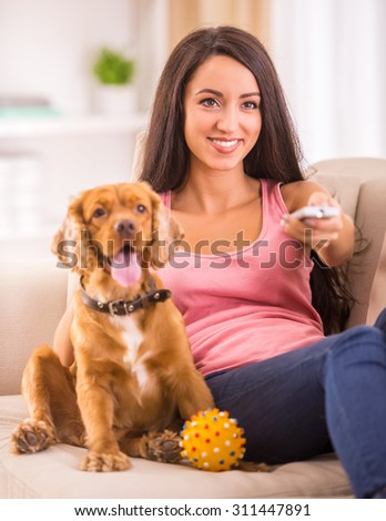Picture of young woman is watching tv while her dog is lying on sofa near her. - stock photo