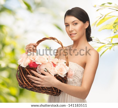 picture of young woman with basket full of flowers - stock photo