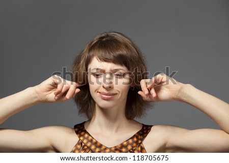 Picture of young woman with fingers in ears