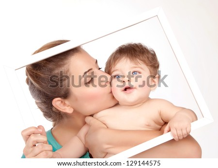 Picture on beautiful young mother kiss her little son isolated on white background, pretty female with cute naked child in white frame, happy childhood, health care, cheerful family, love concept - stock photo