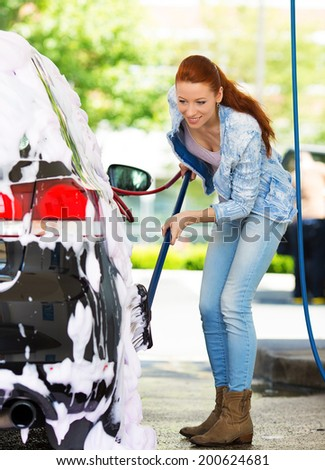 Picture, portrait young, smiling, happy, attractive woman washing automobile at manual car washing self service station, cleaning with foam, pressured water. Transportation, auto, vehicle care concept