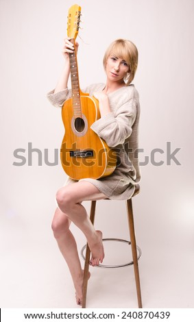 Picture presents Young blonde lady in gray sweater sitting on chair and playing acoustic guitar - stock photo