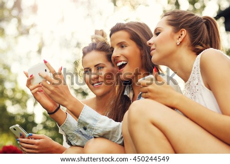 Picture showing group of girlfriends using smartphone outdoors - stock photo