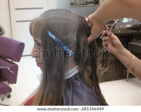 Picture showing hairdresser holding scissors and comb. Close-up hairdresser cutting hair a woman in hairdresser salon.