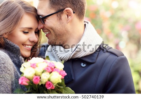 Picture showing happy couple hugging with flowers in the city