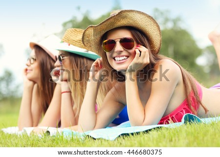 Picture showing happy group of friends lying on the grass and sunbathing - stock photo