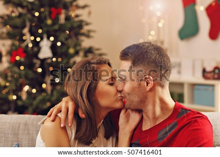 Picture showing young couple kissing over Christmas tree