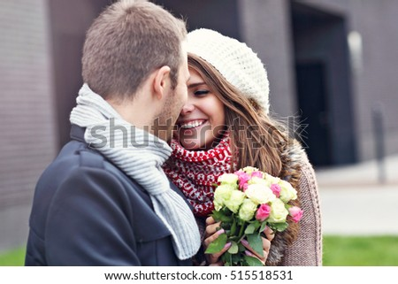 Picture showing young couple with flowers kissing in the city