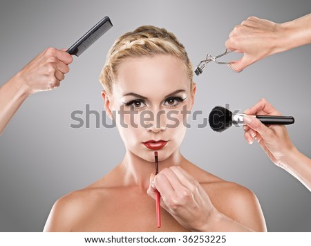 Picture shows studio makeup process hands with brush,lipbrush , lash comb and loose powder brush