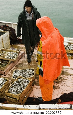 Picture shows two fishermen on a trawler boat on a rainy winter day - stock photo