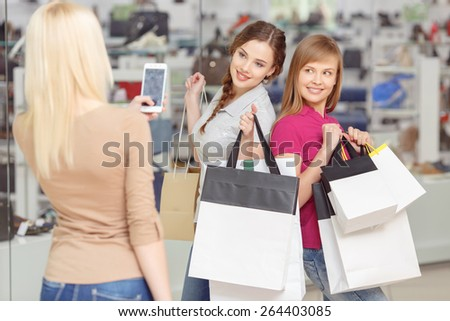 Picture to remember. Two beautiful girls posing for the photo shot made by their friend in the shopping mall - stock photo