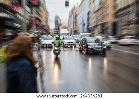 picture with camera made zoom effect of city traffic on a rainy day - stock photo